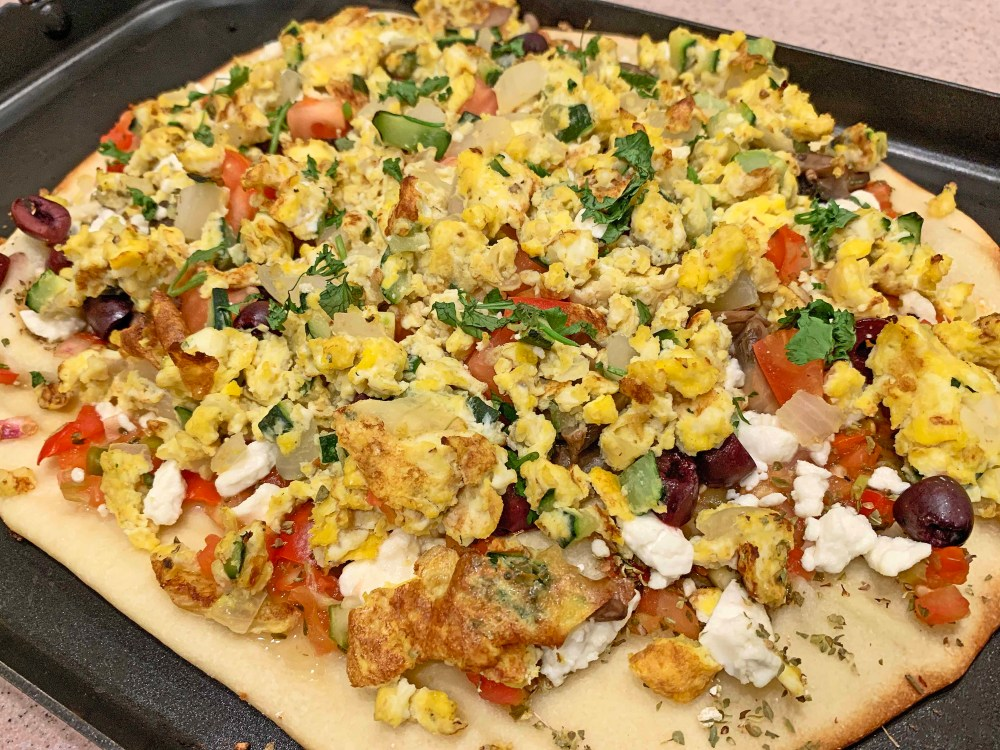 Pizza with yellow scrambled eggs and assorted colorful vegetables on a black pizza pan