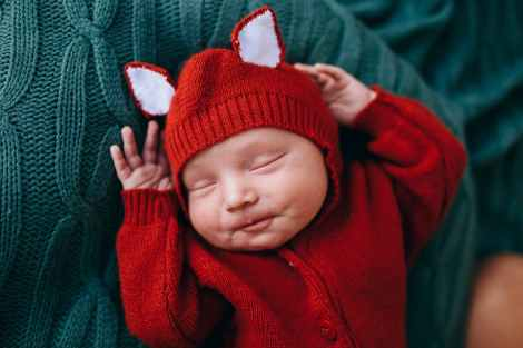 happy cute funny baby in knitted red costume