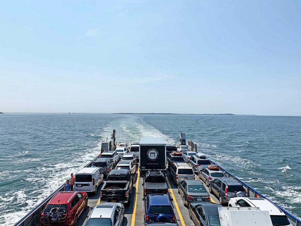 Vehicles on a ferry boat with blue water and blue sky in the background