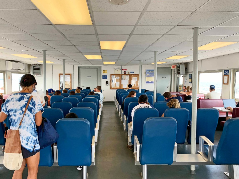 Blue seats on a ferry boat with passengers
