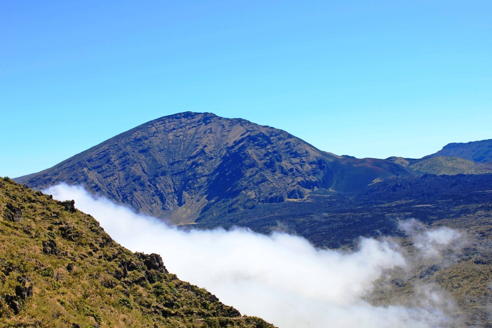 White clouds rolling into Haleakala Crater with blue skies