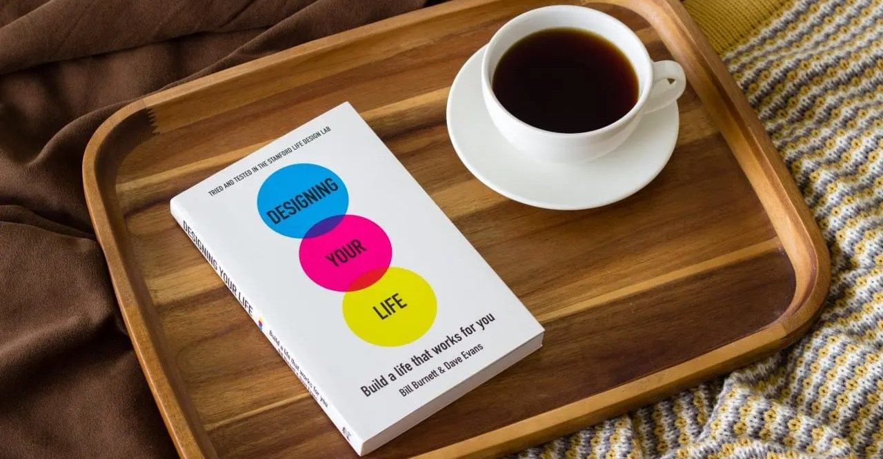 "The book ""Designing Your Life"" and a cup of coffee on a tray"