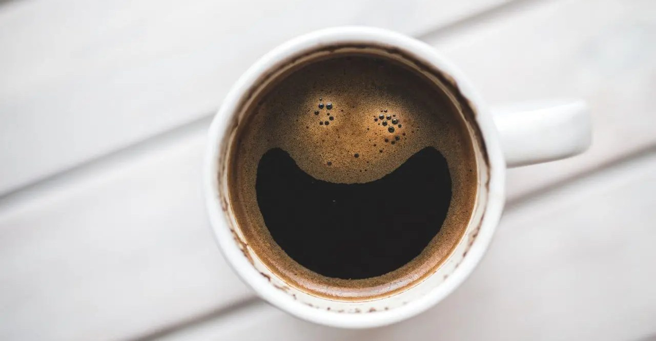 A cup of coffee from above. The foam on the top has the appearance of a pair of eyes and a wide smile.