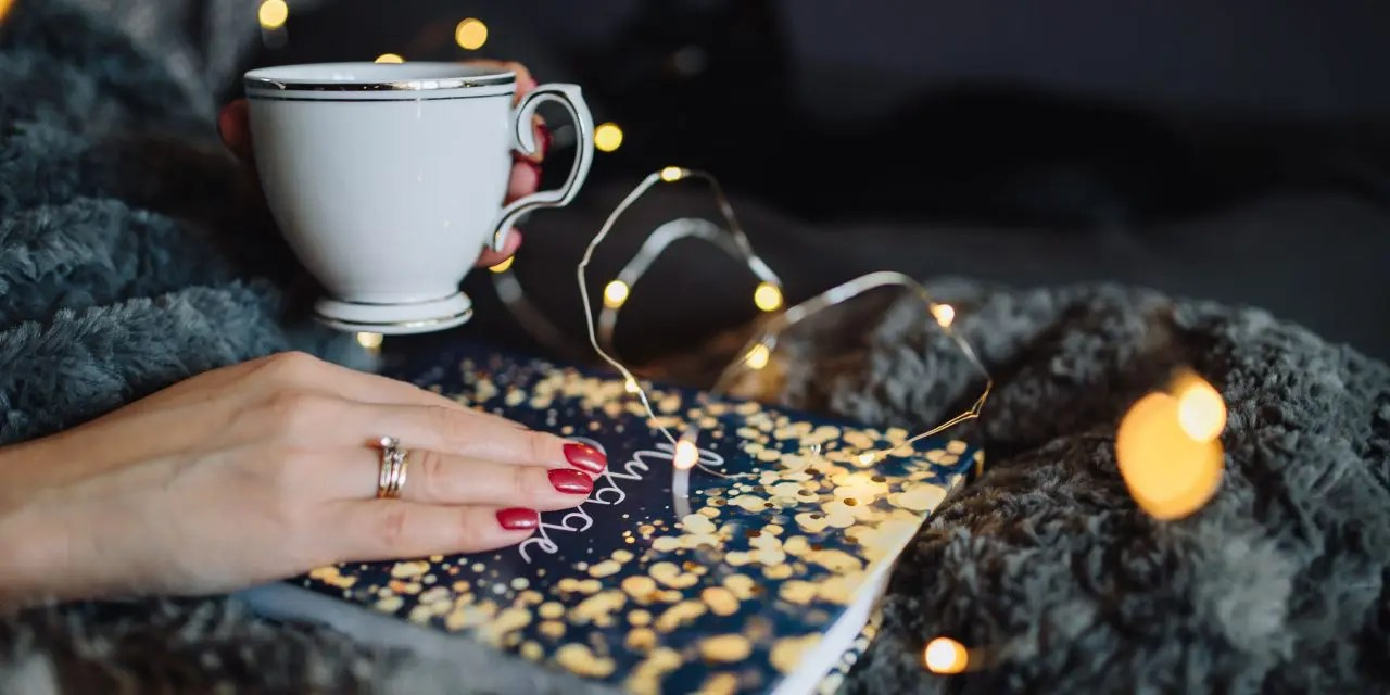 """A woman holding a cup of tea and reading a book entitled """"Hygge"""""""