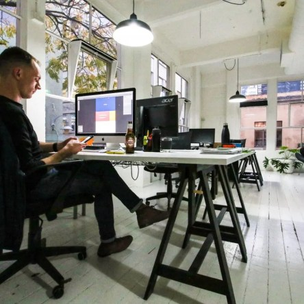Ryan at his desk with a bottle of beer, in a stylish white office