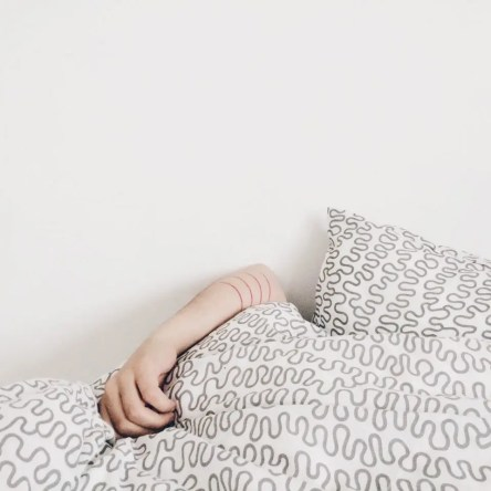 A white woman holds a duvet over her face