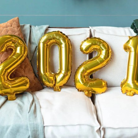 "Four gold inflatable balloons resting on a couch spell out ""2021"""