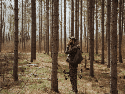 a turkey hunter calling in a forest