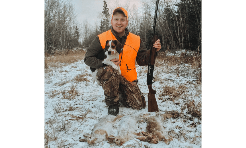 A hunter with a beagle and snowshoe hares