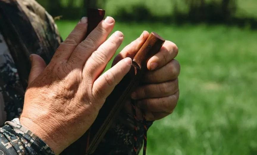 A turkey hunter uses a box call to locate turkeys.