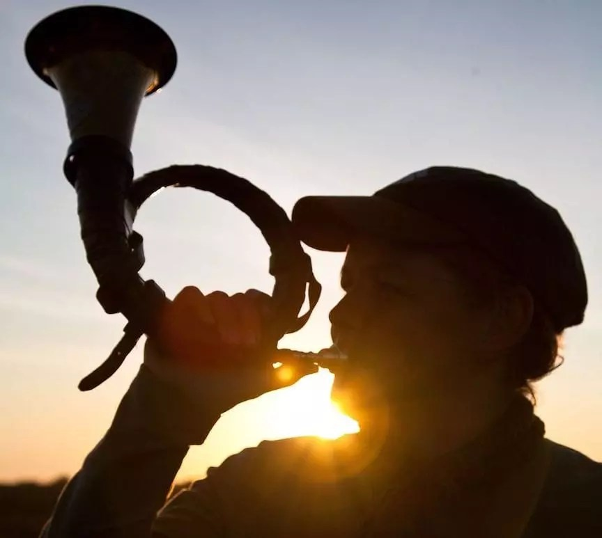 A German hunter blows the traditional hunting horn at sunset