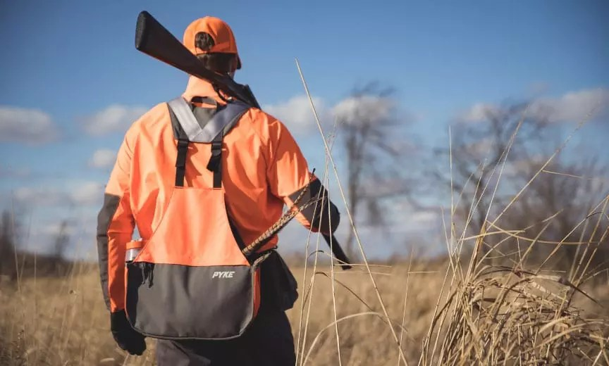 A hunter walks in a field with a pyke vest on.