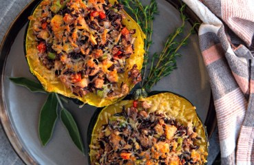 Two halves of stuffed acorn squash on a seasonal plate