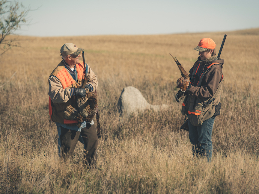 Two pheasant hunters standing in a fall field