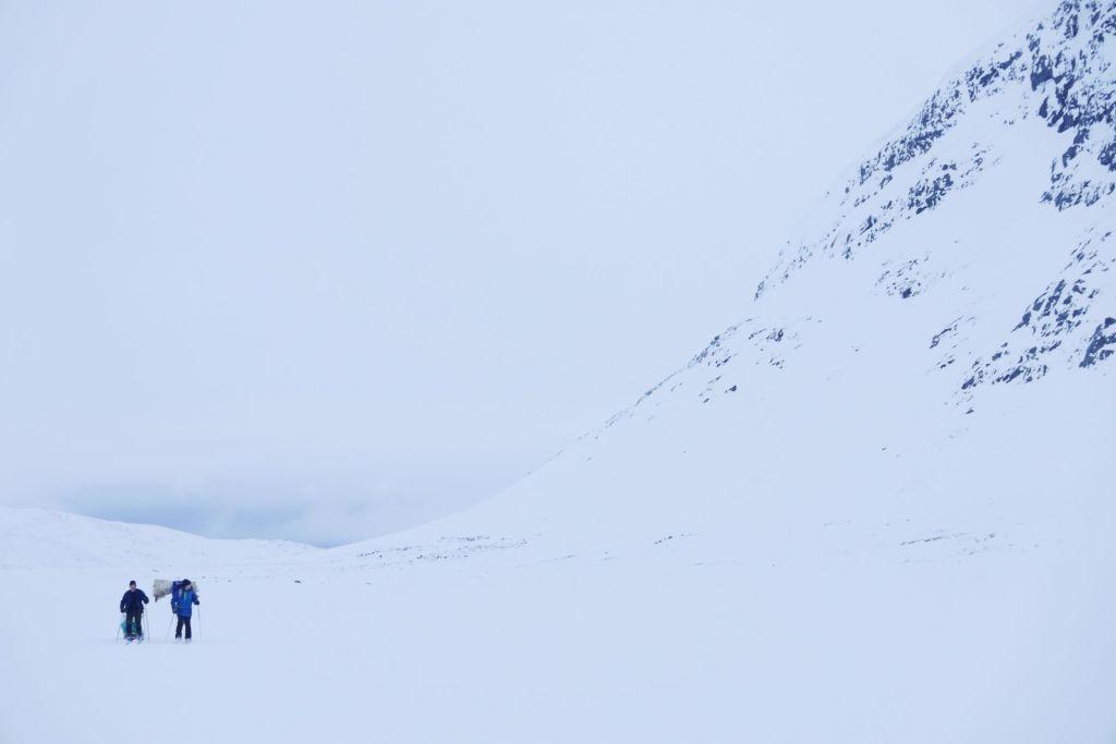 Två människor skidar bredvid ett stort fjäll