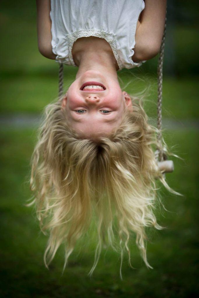 En flicka hänger upp och ner i en repstege