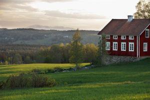 Vybild med rött hus och fjällen bakom