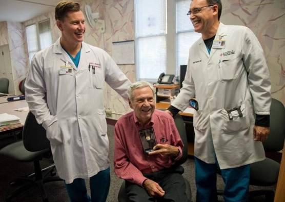 Jim Affleck ţinând în mână supapa cu care chirurgii cardiologi Robert Kincade (stânga) şi David Roberts (dreapta) au reuşit să îi salveze problemele valvei aortice care îi puneau viaţa în pericol.