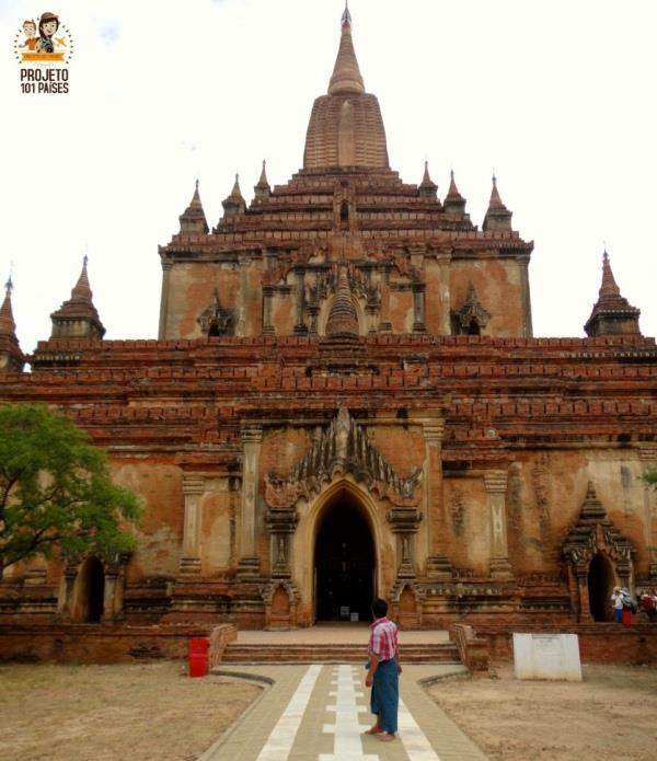 Um local com vestimenta típica (Longyi) na entrada da Sulamani Guphaya