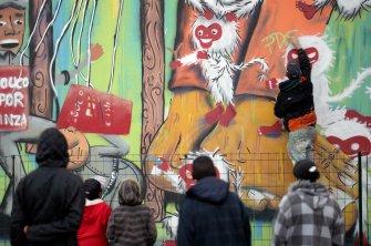Moradores assistem o artista Subtu finalizando o seu primeiro mural.