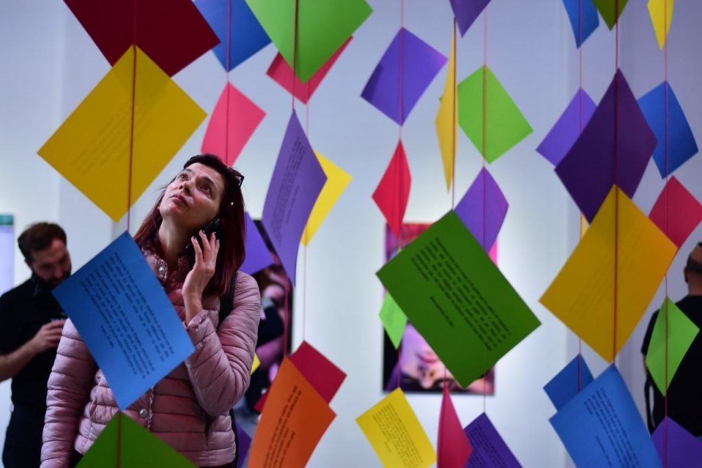 Person with audio device stands amid colored paper suspended from ceiling by red yarn