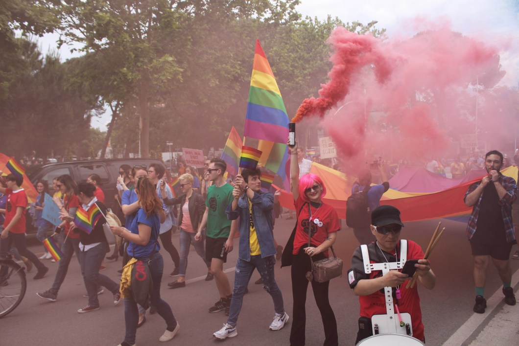 Pride parade marchers with Rainbow flags and pink smoke