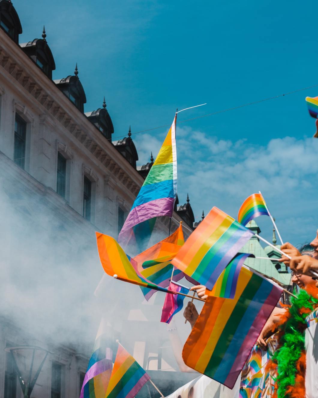 Hands waving rainbow flags against a skyline and sky