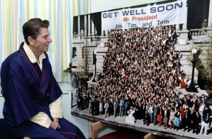 """President Reagan looking at """"Get Well Soon Mr. President"""" photo while at George Washington Hospital. 4/8/81. (Reagan Library)"""