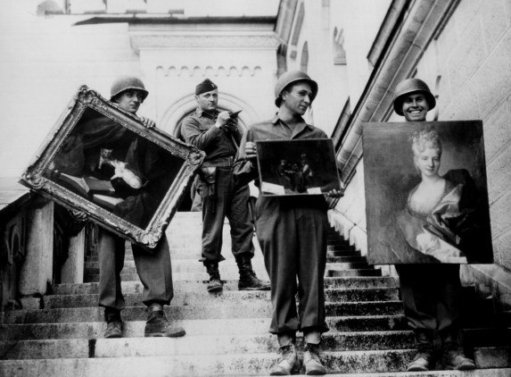 Monuments, Fine Arts, and Archives (MFAA) Officer James Rorimer supervises U.S. soldiers recovering looted paintings from Neuschwanstein Castle in Germany during World War II, April-May, 1945.