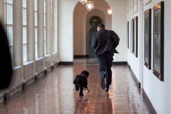 President Barack Obama runs down the East Colonnade with family dog, Bo, on the dog's initial visit to the White House, March 15, 2009. (Barack Obama Presidential Library, National Archives)