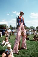 """An """"Uncle Sam"""" character walking on stilts near the Washington Monument during the National Victory Celebration honoring the coalition forces of Desert Storm, 6/8/1991. (National Archives Identifier 6481460)"""