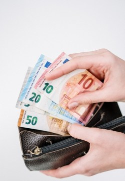 A man holding a wallet full of money. Do you want to be as rich as him? Hurry up and start a lashes business at home.