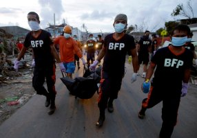 Firemen carry the newly recovered body of a victim of Typhoon Haiyan in Tacloban, central Philippines, Wednesday, November 13, 2013. (Photo by Dita Alangkara/AP Photo)