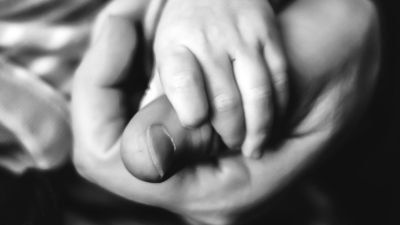 Baby holding Father's thumb
