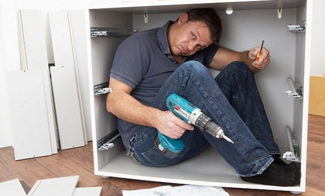 man stuck in a kitchen doing diy before selling his house