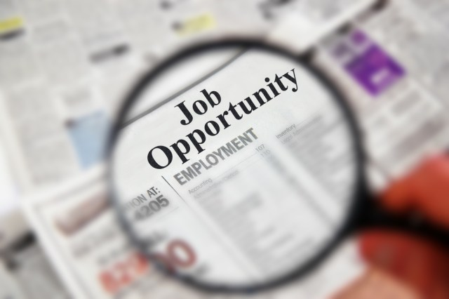 Job Opportunity in Newspaper under magnifying glass for Apartment Manager Jobs