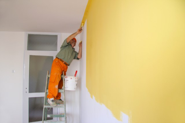 Painter In Action On A Ladder Painting Walls Yellow in Apartment Hiring Apartment Painting Contractors