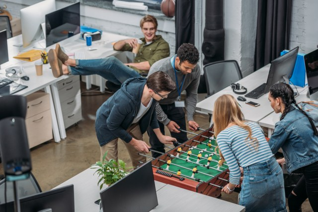 Game Room And Work Share Space With Apartment Residents Playing Table Soccer For Top Apartment Amenities to Attract Millennials