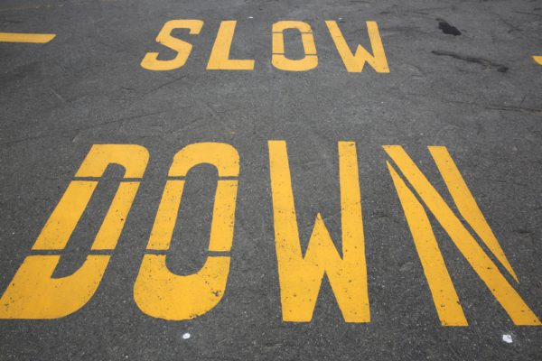 Slow Down Striped On Asphalt Roadway In Yellow Paint For Dealing With Speeders At Your Property