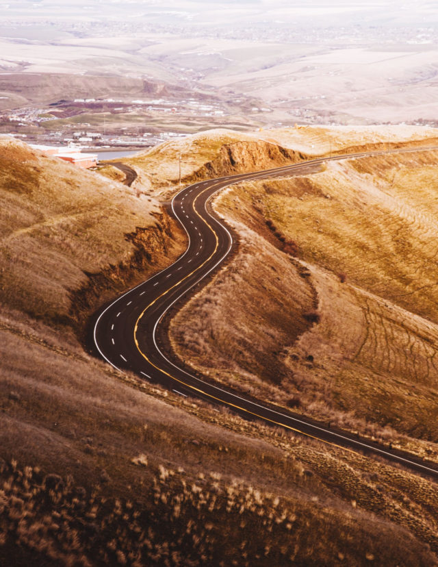 Colored photograph of road winding through brown, treeless hills towards a city.Syria to blame.