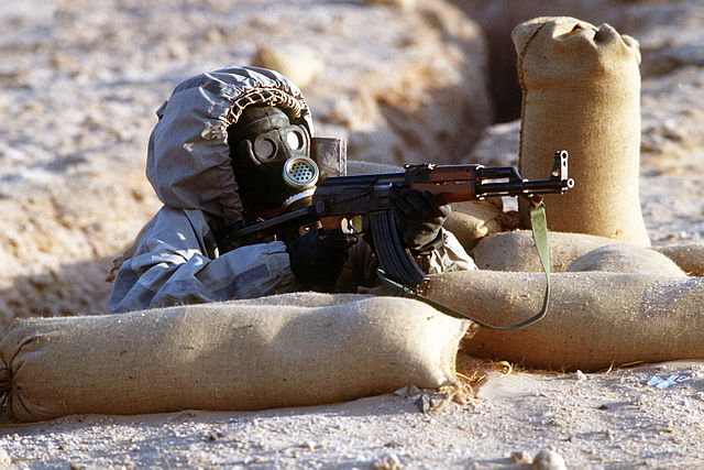 Colored photograph of soldier in chemical warfare protective gear, aiming a weapon. Syria to blame?