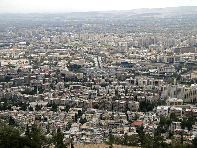 A colored photo of part of the city of Damascus with many buildings crowded together, and a few trees in the foreground. Syria to blame?