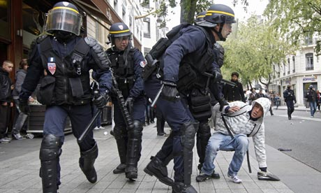 Colored photograph of  group of heavily armed policemen on a road or plaza. One of them is grabbing a civilian by the arm. Is France in prophetic scriptures?