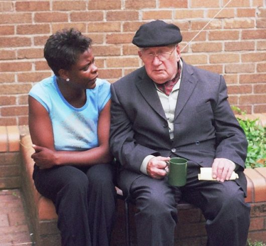 Colored photograph of young woman sitting on brick garden edging beside an elderly man. Is France in prophetic scriptures?