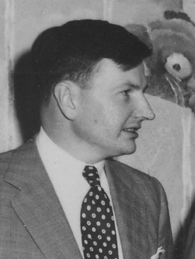 Black and white profile photograph of David Rockefeller as a young man, wearing a suit with black and white polka-dot tie. The very definition of a globalist.