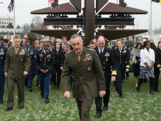 Assembled military commanders in khaki and navy uniforms walking away from the NATO Star rusted steel sculpture. Israel embraces NATO