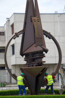 Two workmen in fluorescent green vests prepare to move rusty steel NATO sculpture to new NATO headquarters. Israel embraces NATO