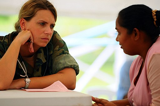 Colored photograph of  young white woman wearing camouflage shirt in discussion with Asian woman wearing pink blouse. 200 million horsemen.