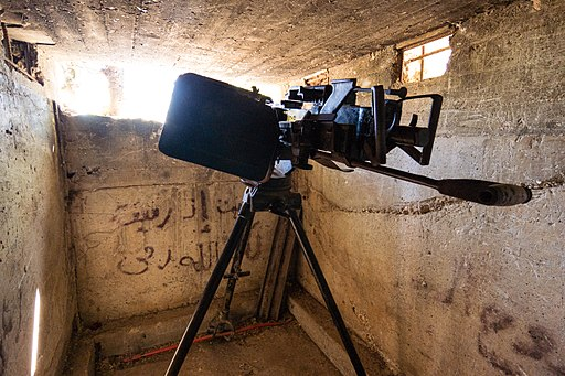 Colored photograph of a blackened heavy machine gun on a tripod inside a concrete fortification. It is positioned to fire through a firing slit. Fiery torch in the sheaves.