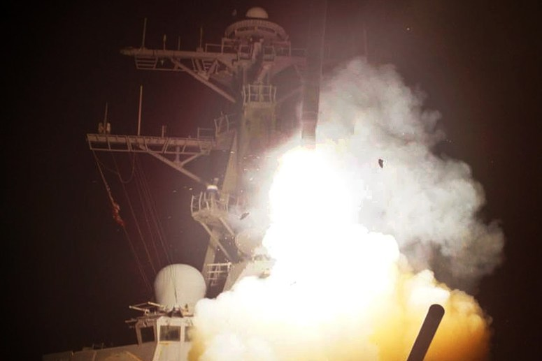 Color photograph of a U.S. warship firing a Tomahawk cruise missile at night. Bridge of warship is gray, silhouetted by white yellow exhaust of missile. Rumors of wars.